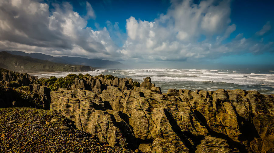 Scenic view of pancake rocks by sea against sky