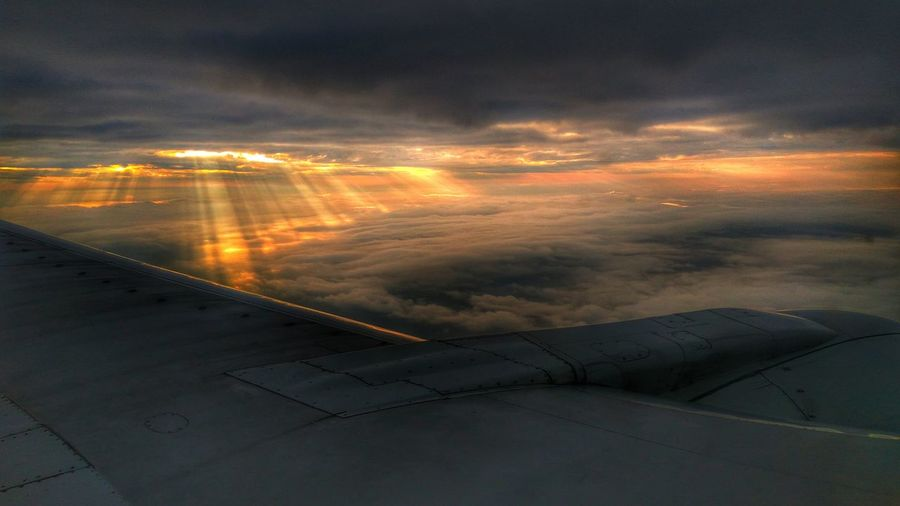 Aerial view of airplane wing against sky during sunset