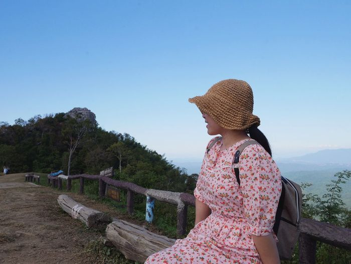 Rear view of woman looking at mountain against sky