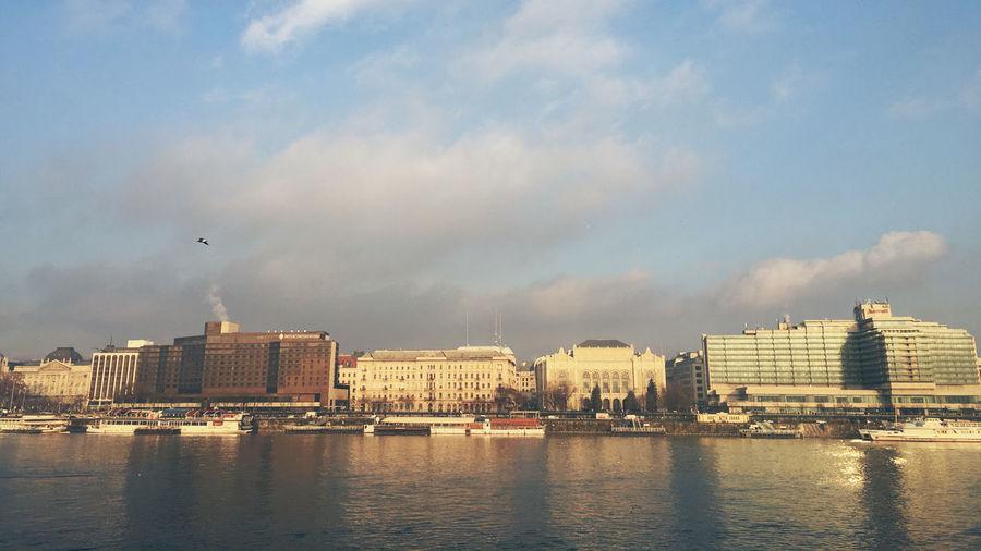 Danube river and buildings against sky in city