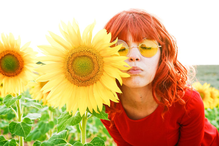 Close-up of beautiful woman wearing sunglasses by sunflower
