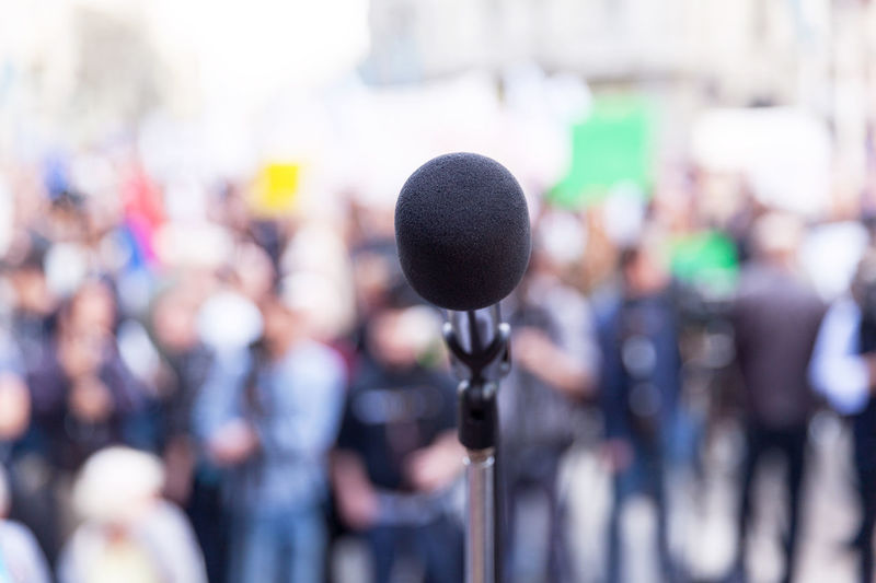 Close-up of a microphone, blurred participants of a protest or political rally in the background Microphone Input Device The Media Group Of People Politics Crowd Speech Audience Event Stage Rally Protest Demonstration Convention Gathering Protesters Elections Propaganda Civil Rights  Public Event Activism Demonstrators Civil