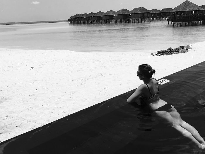 High angle view of young woman wearing bikini swimming infinity pool