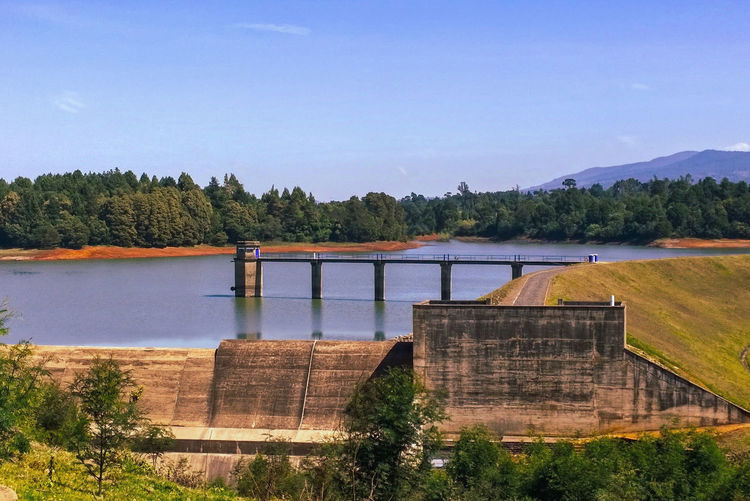 Scenic view of dam by river against sky