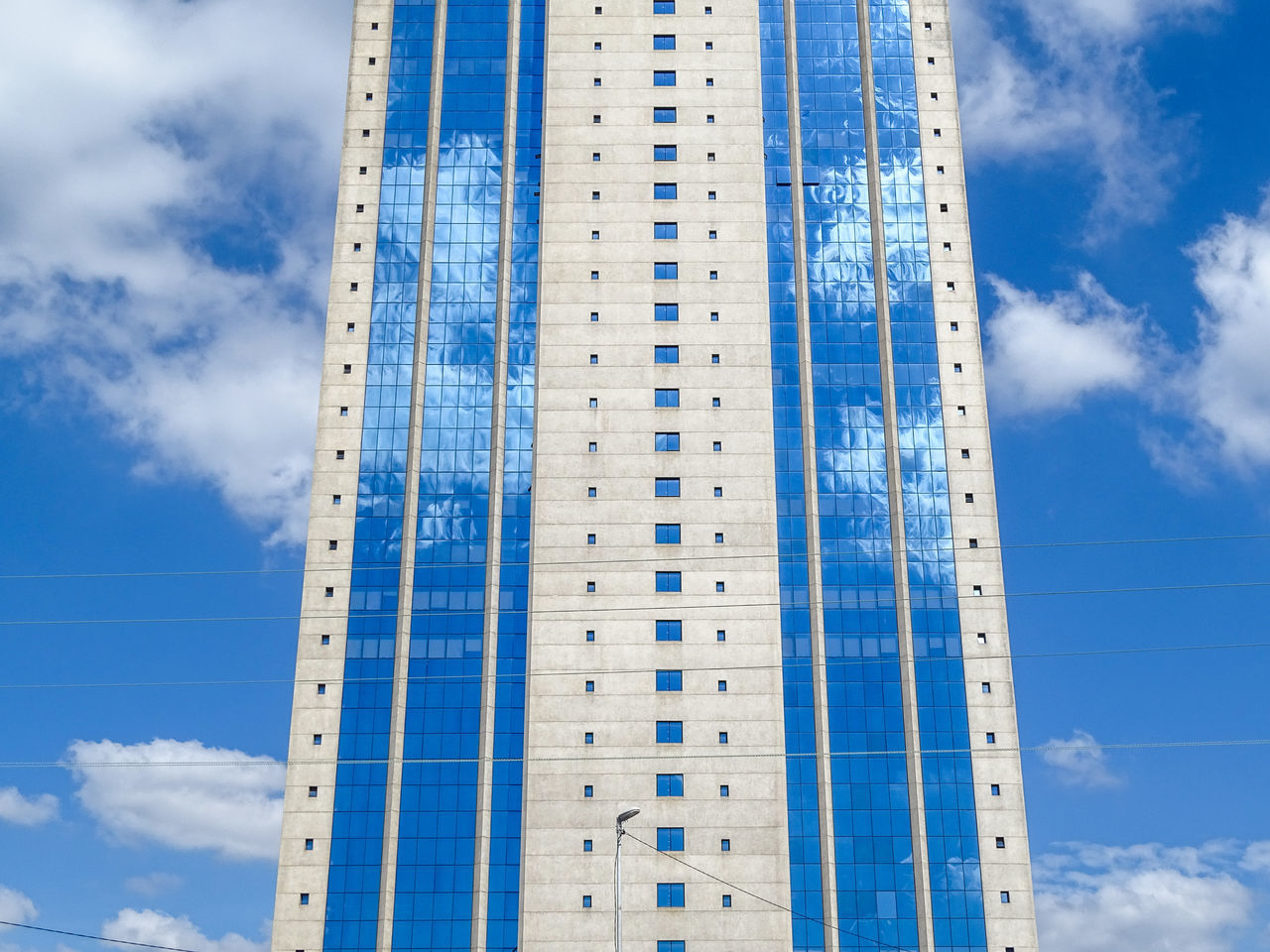 low angle view, sky, blue, cloud - sky, architecture, modern, built structure, skyscraper, day, no people, building exterior, tall, outdoors, city, nature