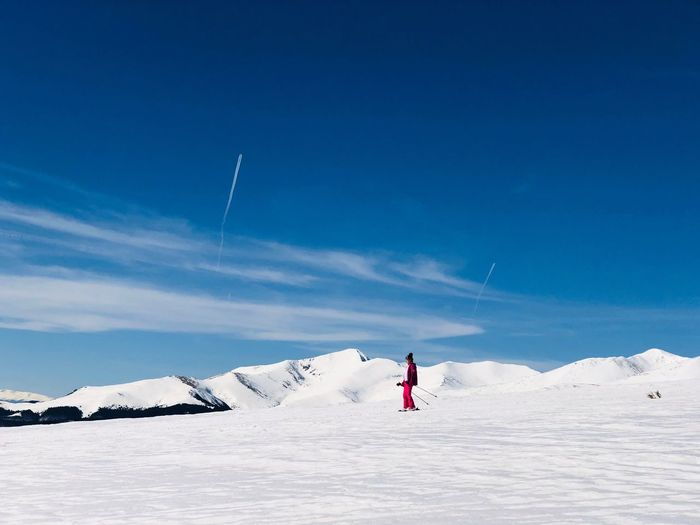 Woman skiing on snow covered land against sky