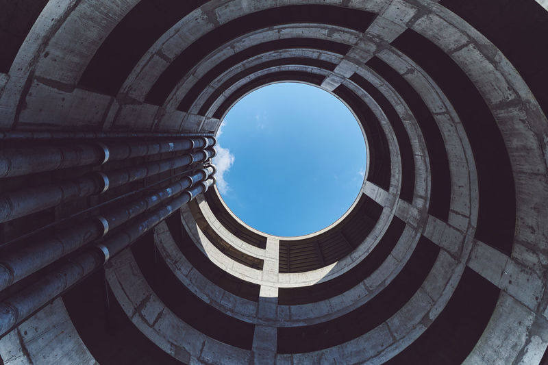 Low angle view of spiral building against blue sky