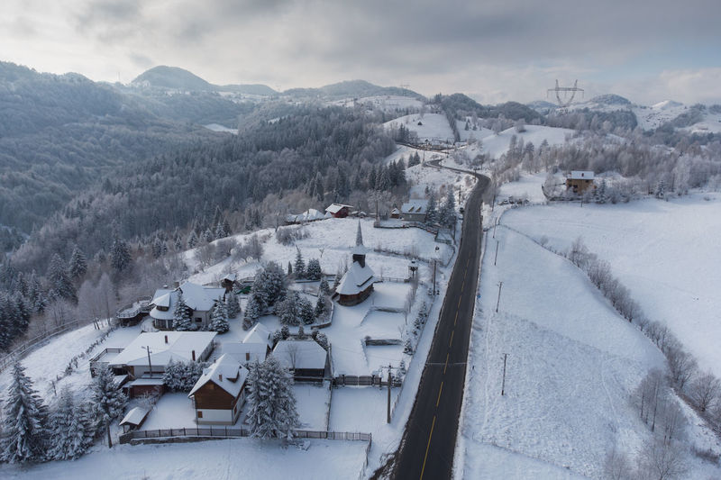 High angle view of snow covered houses by buildings against sky