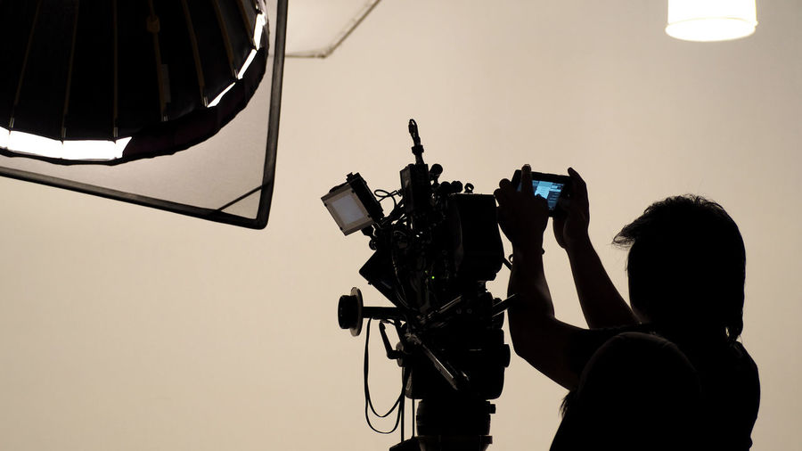 Silhouette of photographer checking for movie camera and set before shooting in studio. Camera Operator Digital Director Equipment Film Film Industry Film Photography Film; Set; Camera; Tv; Movie; Making; Studio; Crew; Video; Behind; Screen; Television; Big; Team; Recording; Man; Background; Professional; Scenes; White; Shoot; Silhouette; Director; Person; Photography; Scene; Producer; Production; Backdrop; Industry; U Filming Men MOVIE Movie Camera People Production Rear View Studio Technology Video