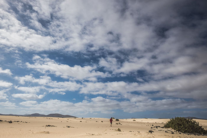 Alone young man walking in the desert of Fuerteventura Fuerteventura Adventure Arid Climate barefoot Beauty In Nature Cloud - Sky Day Desert Landscape Mammal Men Nature One Person Outdoors People Real People Red Jacket Sand Sand Dune Scenics Silence Sky Solitude Tranquility Young Boy