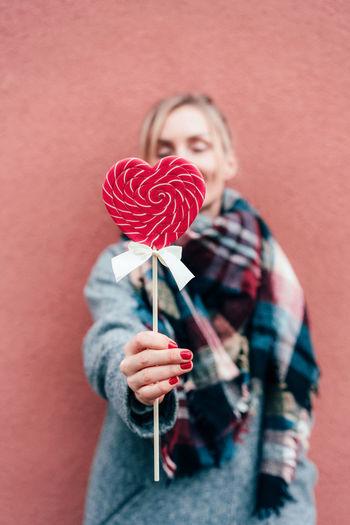 Woman holding heart shaped lollipop against wall