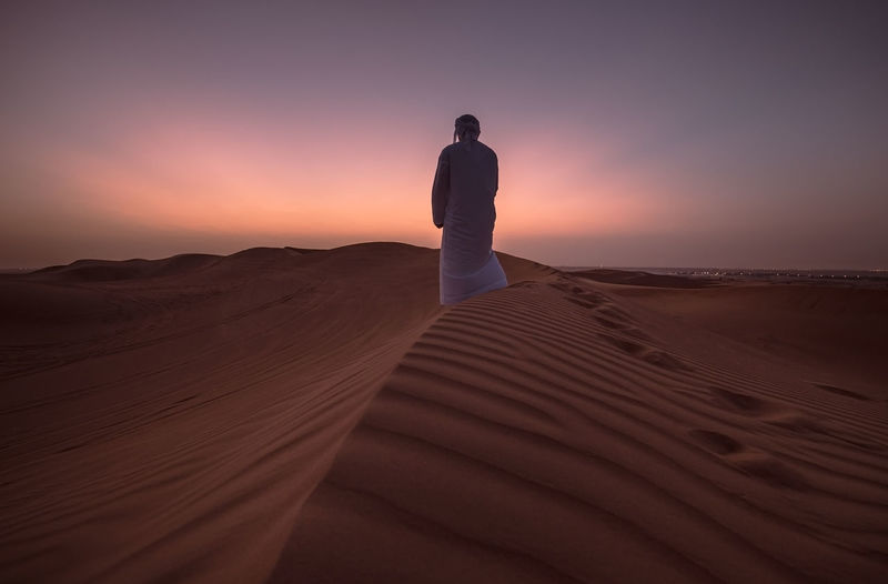 Desert Scenics - Nature Landscape Land Sand Dune One Person Tranquil Scene Beauty In Nature Sunset Environment Sky Sand Tranquility Remote Arid Climate Rear View Climate Non-urban Scene Nature Solitude Outdoors Man Emirati Arab Man UAE