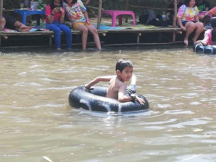 Siblings sitting in water