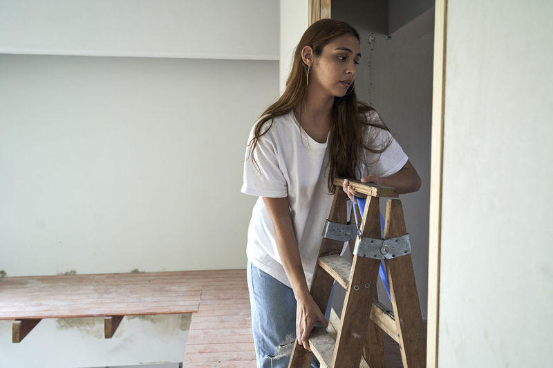 Young woman standing against wall at home