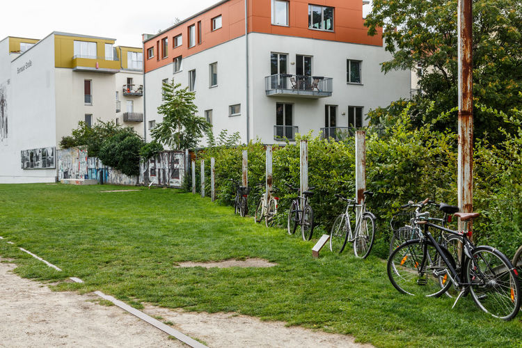 Bicycle by house on field against buildings