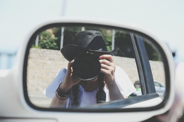 Reflection Of Woman Photographing Using Camera On Car Side-View Mirror