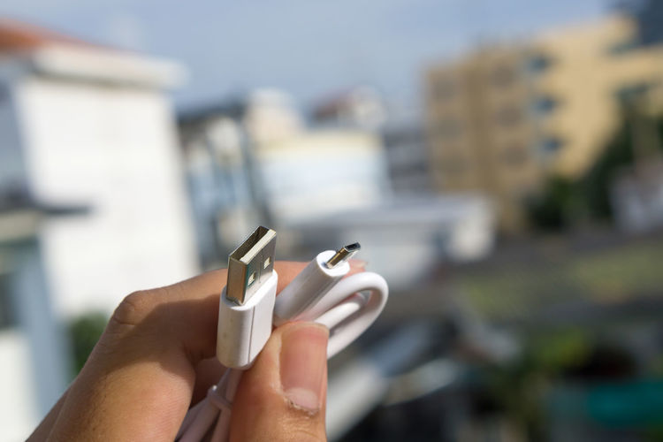 Close-Up Of Hand Holding Usb Cable Against Buildings