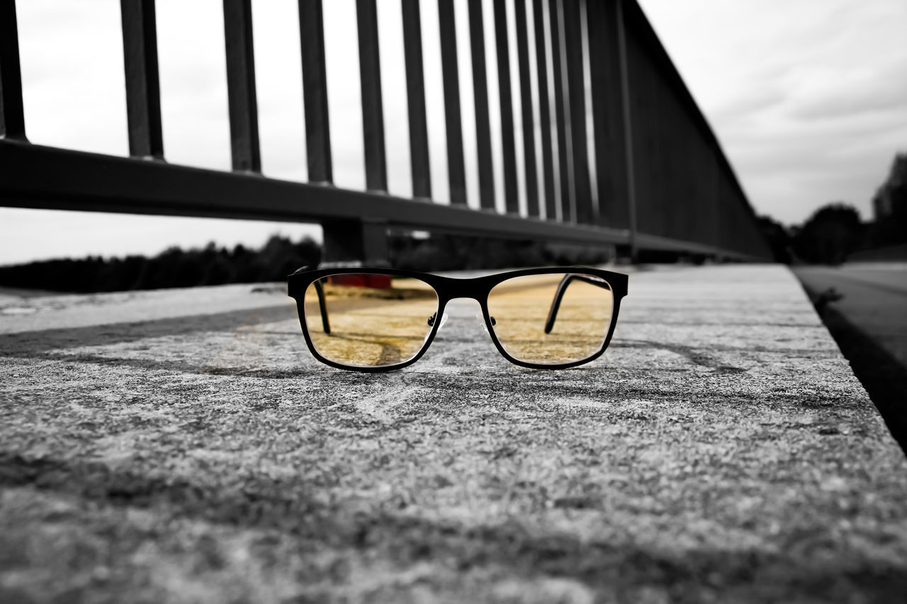 CLOSE-UP OF SUNGLASSES WITH EYEGLASSES ON STREET