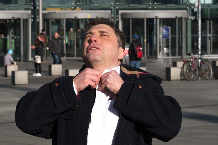 Stressful businessman adjusting shirt in city
