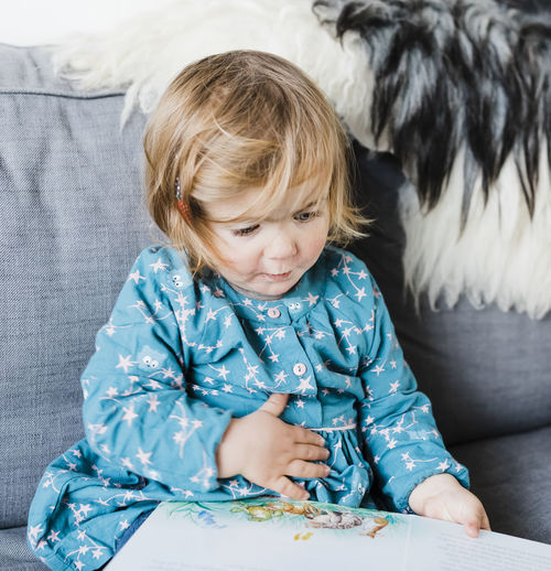 Toddler girl sitting on sofa and reading picture book - Hindeloopen, Friesland, Netherlands Dress Happiness Learning Looking Down Picture Book Reading Sitting Blond Hair Book Child Childhood Close-up Cute Education Front View Germany Girl Indoors  Living Room One Person Portrait Sofa Toddler  Toddlerlife Waist Up