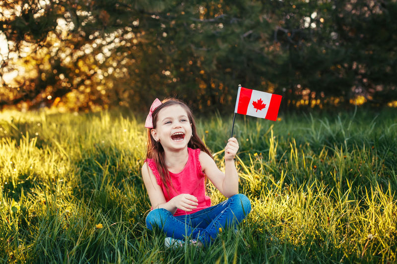 Happy girl with canadian flag sitting on field