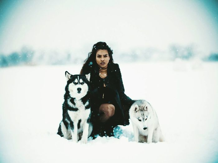 Portrait of woman with dog sitting on snow