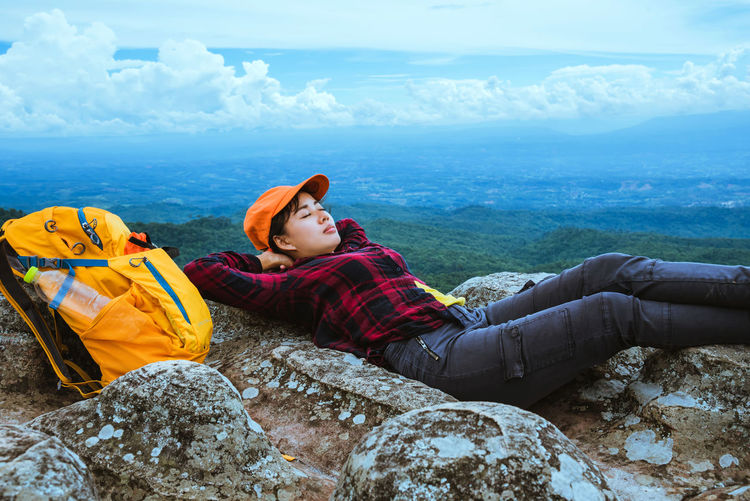 Female hiker lying on cliff against landscape
