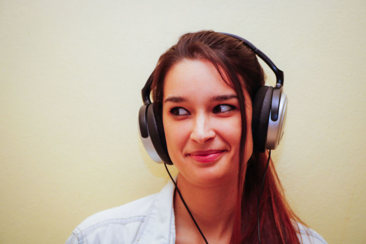 Close-up of woman looking away while wearing headphones against wall
