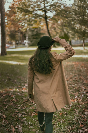 Rear view of woman walking in park during autumn