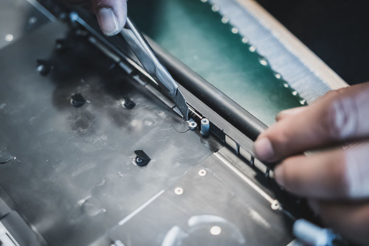 Cropped hands of technician repairing computer part