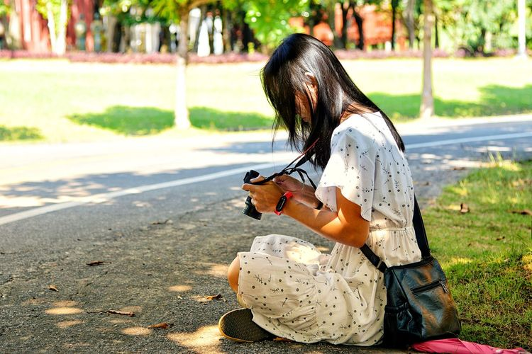 Side view of woman using camera while sitting by road