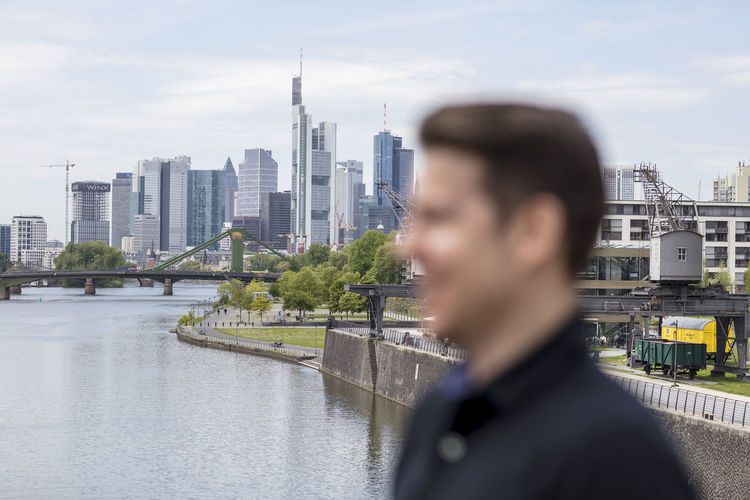 Frankfurt's skyline and a man's face in blurred profile. Close up. Adult Architecture City City Centre Cityscape Frankfurt Am Main Man Profile Shallow Depth Of Field Skyline Skyscrapers Bridge Caucasian Ethnicity Close Up Clouds Distance Germany Golf Shirt Hairstyle Main River Metropolis Modern Building River Short Sleeved Urban