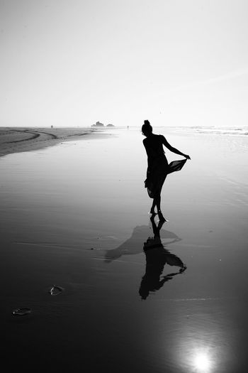Silhouette Woman Wading In Sea Against Sky