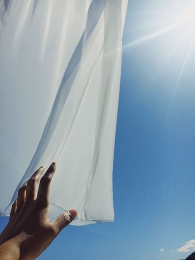 Cropped hand reaching textile against sky