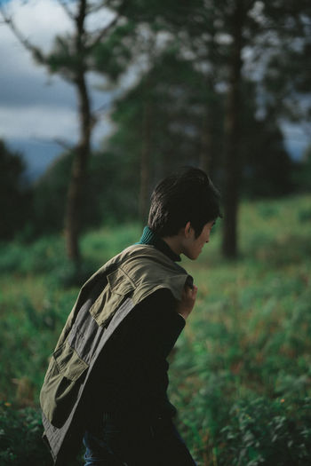 Side view of young man walking in forest against trees