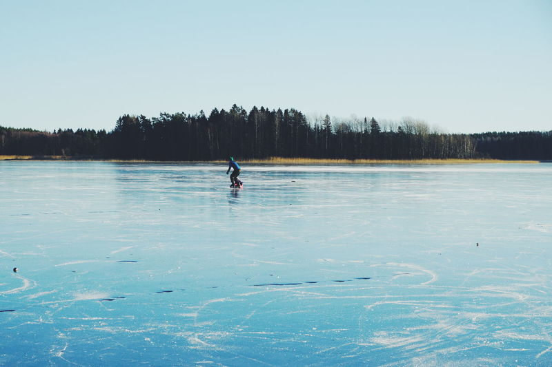 Person ice-skating on frozen lake against clear sky