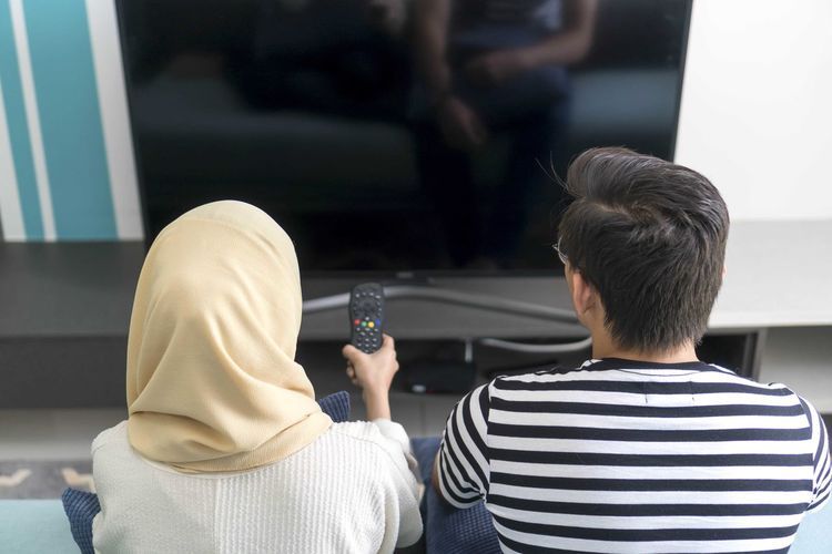 Young Malay Couple at the Sofa watching tv together Rear View Men Real People Lifestyles People Casual Clothing Leisure Activity Sitting Males  Indoors  Adult Striped Women Focus On Foreground Two People Communication Headshot Portrait Technology