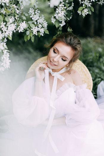 Beautiful bride in a wedding dress walks in a blooming apple-tree park in spring