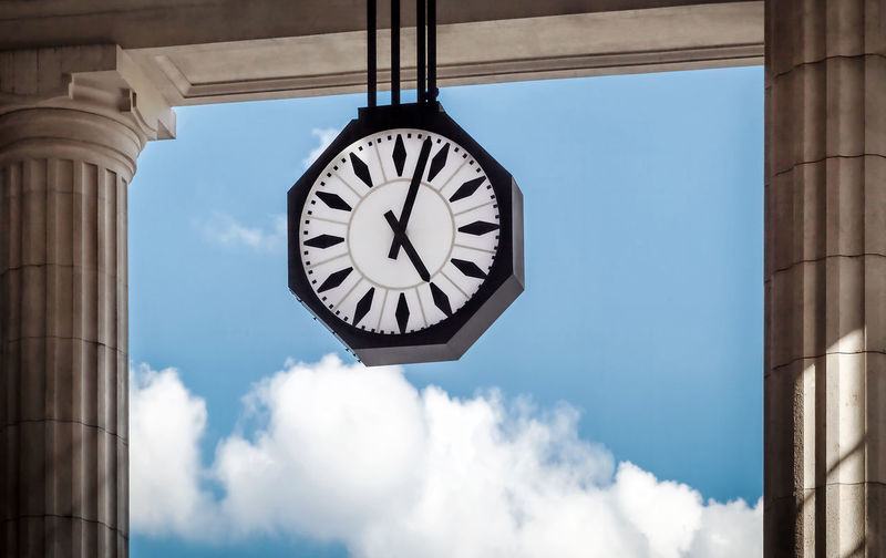 The clock of the Central Station in Milan, Italy, stands between the columns of the porch in front of the lobby. In the background a blue sky with a few passing clouds.