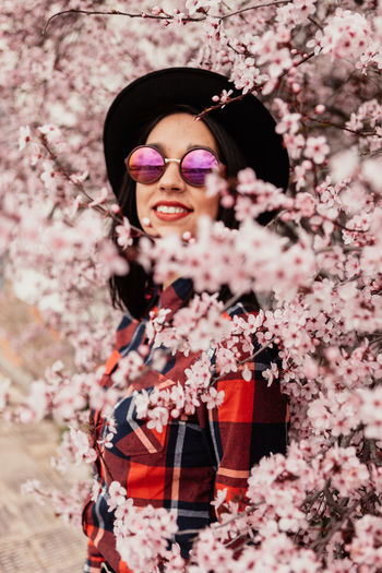 Portrait of woman wearing sunglasses standing by cherry blossom
