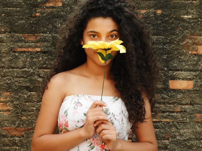 Portrait of beautiful teenage girl with artificial flower standing against brick wall