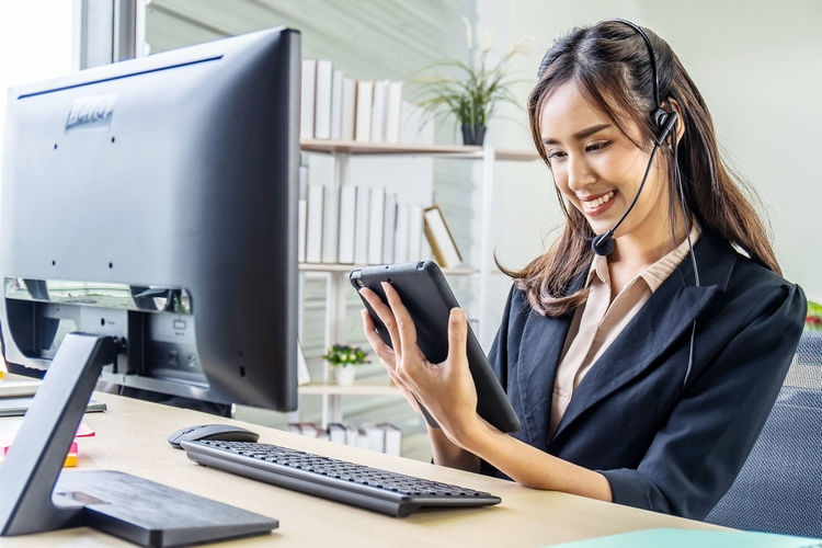 Woman working with smart phone on table