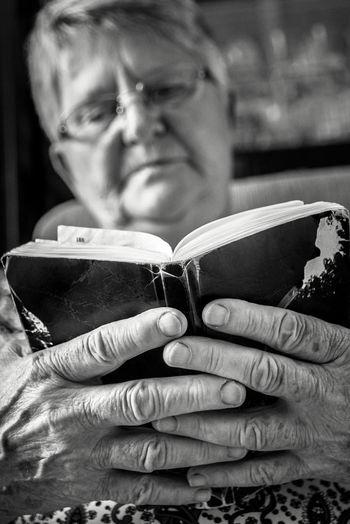 Senior Woman Wearing Eyeglasses Reading Book At Home