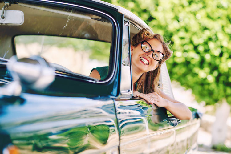Beautiful happy woman sitting in a car. Retro styled Driving Sitting Auto Beautiful Woman Car Day Drive Eyeglasses  Eyeglasses  Land Vehicle Mode Of Transport One Person Outdoors Pretty Real People Retro Car Retro Styled Smiling Spectacle Sunny Day Transportation Vinatge Women Young Adult Young Women