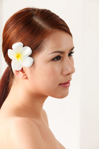 Close-Up Of Woman Wearing Flower Against White Background