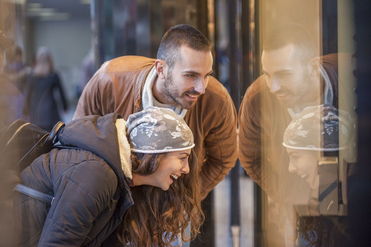 Midsection of couple looking at shop window