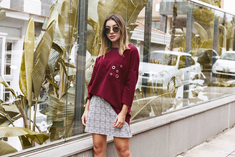 Portrait Of Young Woman Standing On Sidewalk By Glass Building