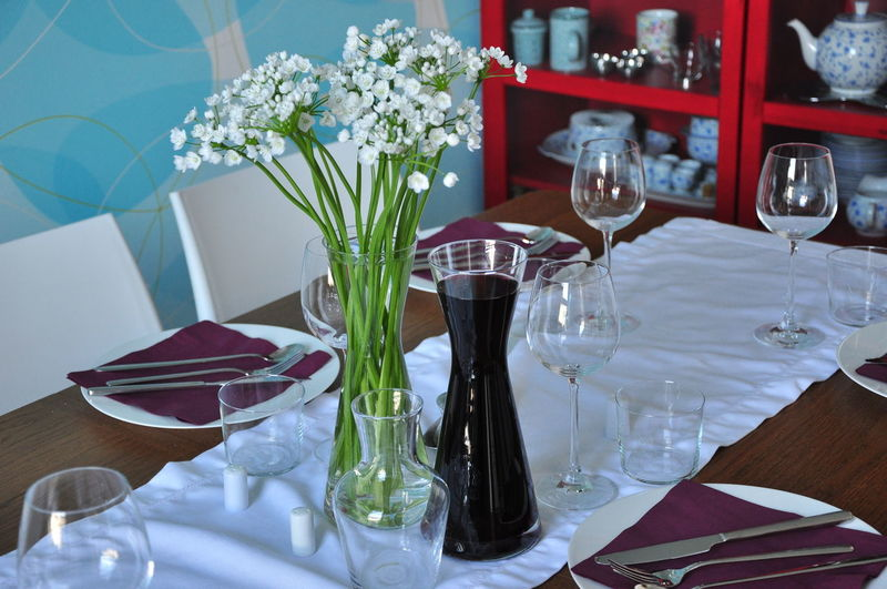 Drink With Wineglasses And Flower Vase Arranged On Dining Table