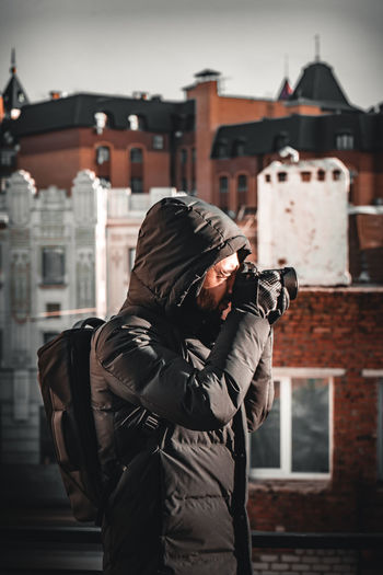 Midsection of man photographing against building in city