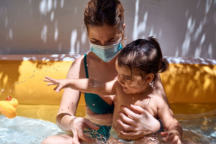 Young mother with a mask in an inflatable pool with her little daughter. safe holiday concept